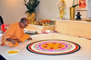 Puja mit Swami Nivedananda mit Mandala aus farbigen Pulvern
