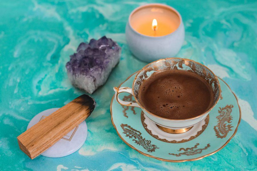 Kerze, Edelstein, Räucherwerk und Tee auf einer Oberfläche