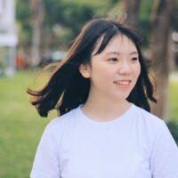 Frau lächelt offenherzig mit Wind im Haar