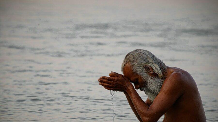 Mann betet im Fluss